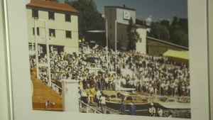 Valokuva ihmisjoukosta yleisönä pienessä satamassa.