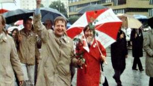 Olof och Lisbet Palme under ett rödvitt paraply med blommor i händerna.