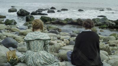 Charlotte (Saoirse Ronan) och Mary Anning (Kate Winslet) sitter på en strand och ser ut över havet.