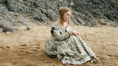 Charlotte (Saoirse Ronan) sitter på en strand och ser allvarlig ut.