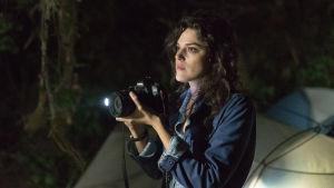 Lisa (Callie Hernandez) håller i en kamera och tittar ut i mörkret.