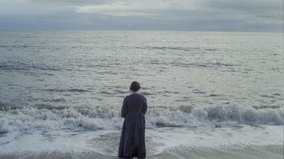 Mary Anning (Kate Winslet) står vid vattenbrynet vid havet och ser mot horisonten.