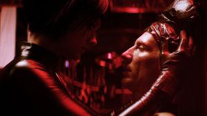 Mona (Krista Kosonen) håller om Juhas (Pekka Strang) huvud i ett mörkt källarutrymme.