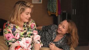 Claire och Béatrice inbegripna i ett förtroligt samtal på en säng.