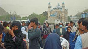 Gata i Kabul med mycket mänskor och byggnad med torn i bakgrunden.