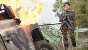 En beväpnad Helen Mirren framför ett brinnande bilvrak.