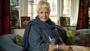Judi Dench poserar i en soffa.