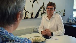Anneli Pahta lyssnar till en person i ett mötesrum.