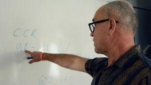 John Hassler pekar mot några siffror och bokstäver han antecknat på en whiteboard.