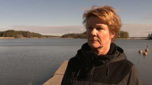 Aktivator Maria Saarinen, en dam med brun jacka, står på en brygga.