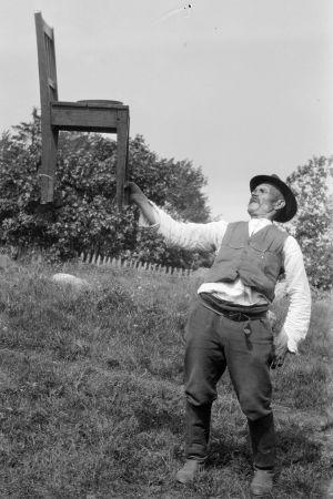 En man lyfter en stol med sin ena hand. Bilden är tagen 1929 i Kungsböle, Strömfors.