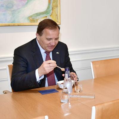 Stefan Löfven och Andreas Norlén vid ett långt bord. De äter jordgubbar.