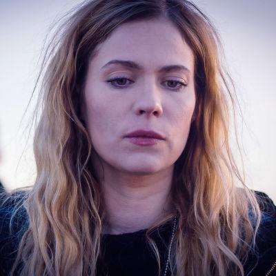 Sofia Karppi (Pihla Viitala) katsoo vakavana jotain alaspäin. Hänen hiuksensa ovat kiharaiset ja auki. Takana kollega Sakari Nurmi (Lauri Tilkanen)