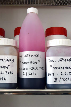 Flaskor med överbliven färg från digital tygtrycksmaskin. På etiketter text, vilken färg det är frågan om och datum.