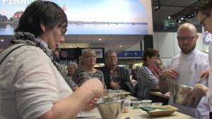 En kvinna står och vispar mittemot två kockar. En liten skara människor tittar på.