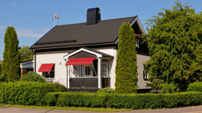 ett hus med röda solskydd ovanför både fönster och dörrar