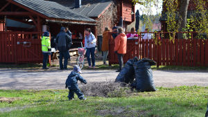 En liten pojke böjer sig ner mot en hög med kvistar. Bakom honom står många människor och diskuterar med varandra.