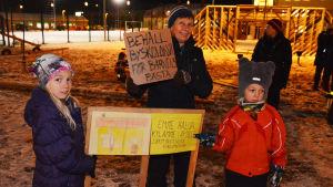 Flera vuxna och barn står utomhus och håller i skyltar. På en skylt står det behåll byskolan för barnens bästa.