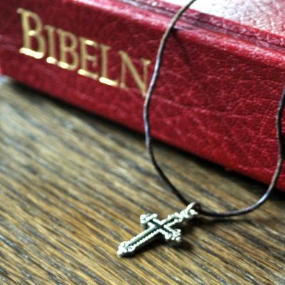 Ett band med ett litet kors är placerat på Bibeln.