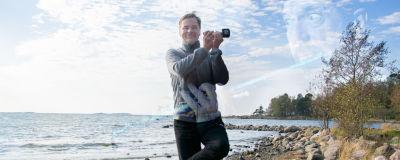 Carl-Kristian Rundman poserar på ett ben på strandsten och låtsas spela fläöjt med Yle-mikrofon. Ian Andersons ansikte bland molnen.