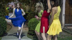 Mia (Emma Stone) viftar på sin blåa klänning och dansar fram påhejad av sina tre väninnor.