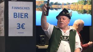 En man klädd i tyska kläder skålar framför en skylt med texten Finnishes bier.