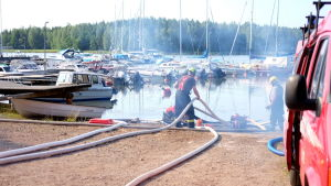 Två brandmän som tar vatten ur en vik.
