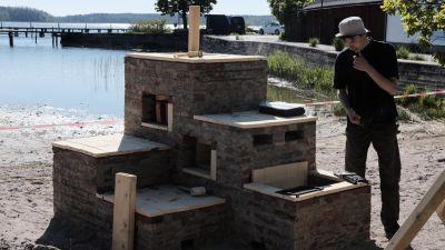 man invid tegelkonstruktion på strand
