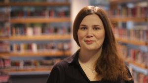 En vit kvinna med brunt, långt hår, står framför bokhyllor i ett bibliotek.