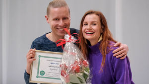 Mies ja nainen poseeraavat iloisesti diplomin ja kukkakimpun kera.