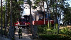 Ett hus som brinner som brandmän försöker släcka.