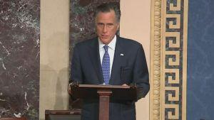 Mitt Romney, en äldre man med grått hår och blå kostym står vid ett talarpodie.