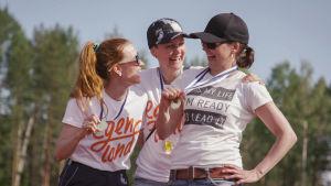 Kolme naista nauraa iloisesti yhdessä mitalit kaulassaan.