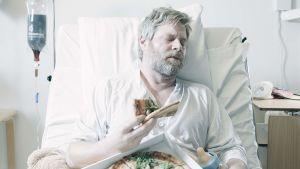Lyhytelokuvan krapulainen mies makaa sairaalasängyssä ja syö pizzaa. Näyttelijä Lukas Loughran