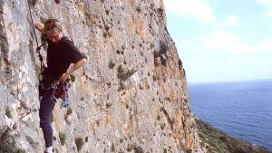 Nainen kiipeää vuorta.