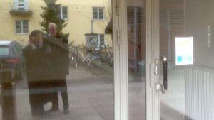 Två personer speglas genom glasdörr