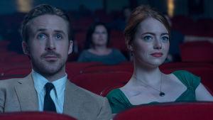 Sebastian (Ryan Gosling) och Mia (Emma Stone) sitter i en biograf och ser på en film.
