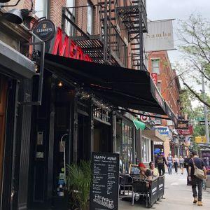 Mercury bars fasad på nionde avenyn, med uteservering, happyhourskylt och blomkruka på trottoaren utanför.