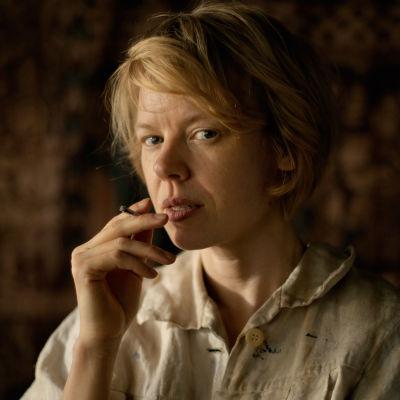 Tove Jansson (Alma Pöysti) står och röker och ser rakt in i kameran.