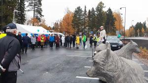 En folksamling står runt några grå vargstatyer. Bredvid statyerna står en man som talar i en mikrofon.