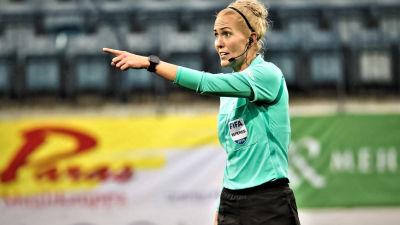 Lina i färd med att utfärda en dom på fotbollsplanen. Hon pekar mot något håll och ser bestämd ut, med headset på huvudet.