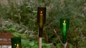 Tre facklor som är gjorda av halverade vinflaskor.