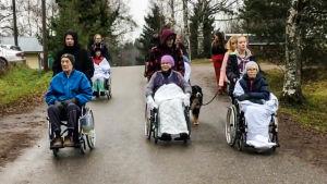 Äldre i rullstol på ledd promenad.