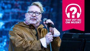 John Lydon bär glasögon och håller i en mikrofon som är i en mikrofonställning.
