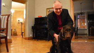 En medelålders man i svart kavaj står på knä och klappar en brun labrador. Hunden tittar in i kameran.