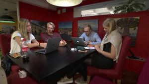 Några unga personer sitter runt ett bord, väggarna är röda.