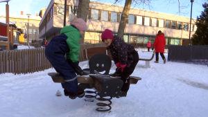 Två flickor gungar på en gunga på en dagisgård.