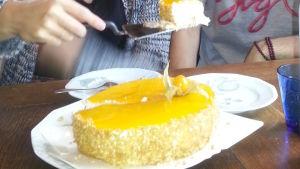 En gul tårta som en hand med en kakspade i har tagit en bit ifrån.
