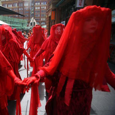 Punaisiin asuihin pukeutuneita ilmastomielenosoittajia Australian Sydeneässä.
