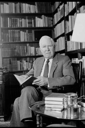 Georg Henrik von Wright sitter i länstol med bok i handen.
